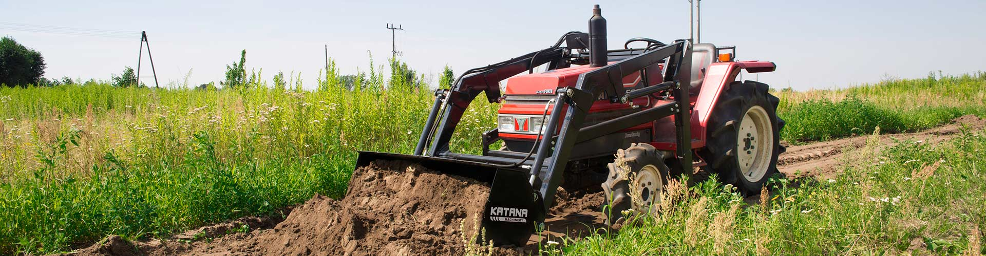 Compact tractor using front loader to leveling ground